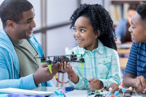 Confident African American dad helps students build a drone in after school engineering club.