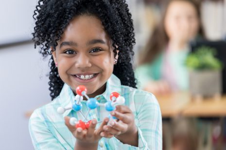 Elementary age school girl smiles at the camera and holds a model of molecular structure